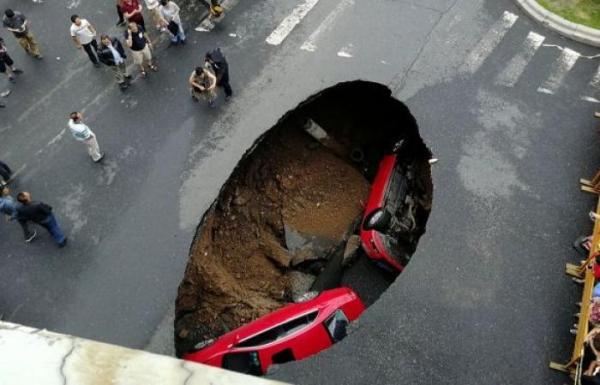 لحظة سقوط سيارة داخل حفرة عملاقة(فيديو)