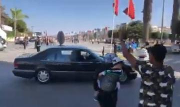 سيدة تعترض موكب الملك محمد السادس في الحسيمة و على ظهرها طفل صغير
